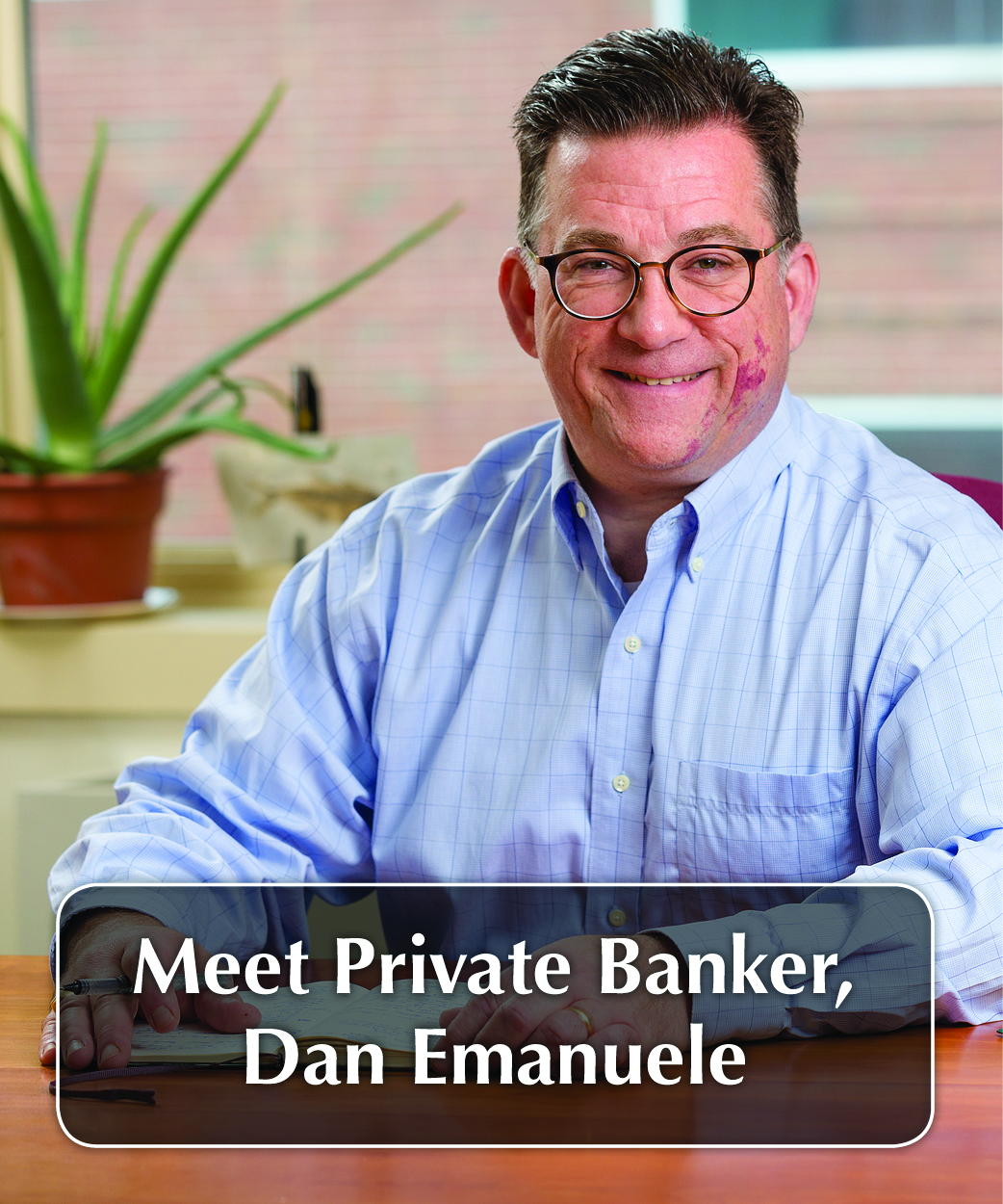 man with glasses smiling at his desk and the words Meet Private Banker, Dan Emanuele