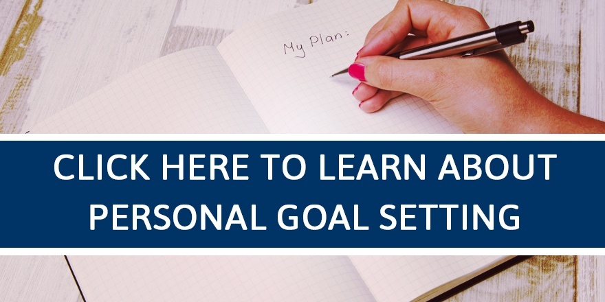 Person writing goals in a journal.