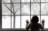 Child looking out window at snow falling on an already snow covered landscape