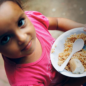 A little girl with a bowl of nourishing food.